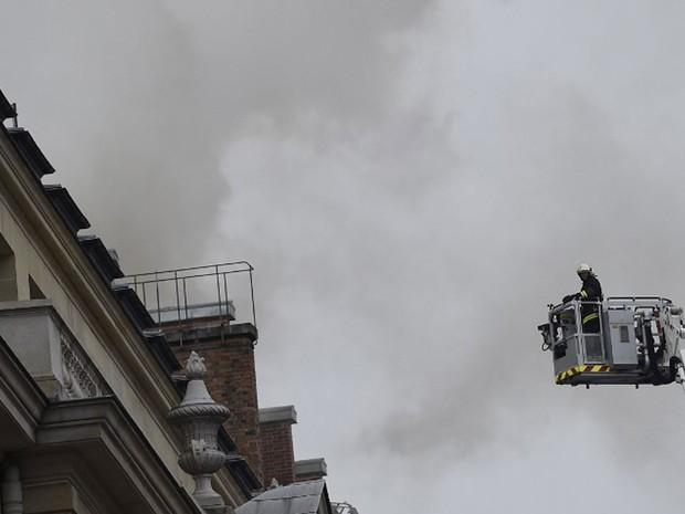 Bombeiro utiliza plataforma para conter chamas no último andar do luxuoso Hotel Ritz, em Paris, nesta terça-feira (Foto: Lionel Bonaventure/ AFP)