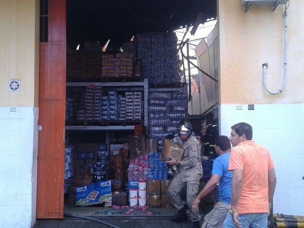 Na outra extremidade do armazém, bombeiro tentava retirar mercadoria de área que não havia sido completamente atingida pelo fogo (Foto: Luís Vítor Melo/G1)