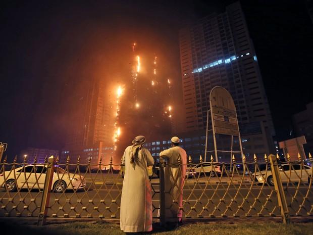 Dois homens observam incêndio nas torres residenciais no emirado de Ajman, nos Emirados Árabes Unidos, na segunda (28) (Foto: AP Photo/Kamran Jebreili)