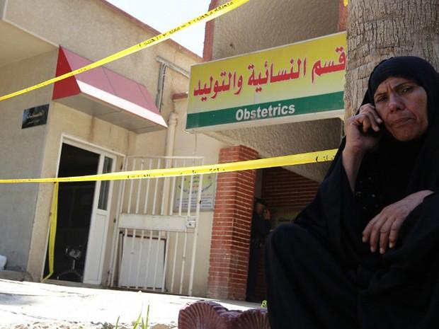 Mulher fala ao telefone em frente ao hospital Yarmuk, em Bagdá, que foi atingido por um incêndio nesta quarta-feira (10) (Foto: Sabah Arar / AFP)