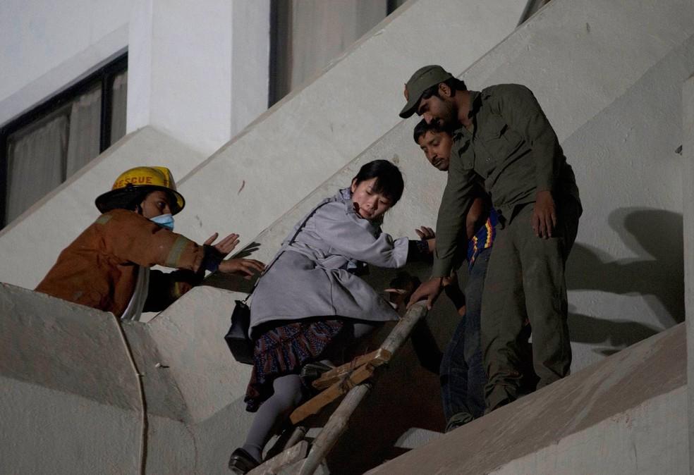 Mulher é resgatada de incêndio em hotel em Karachi (Foto: Shakil Adil/AP)