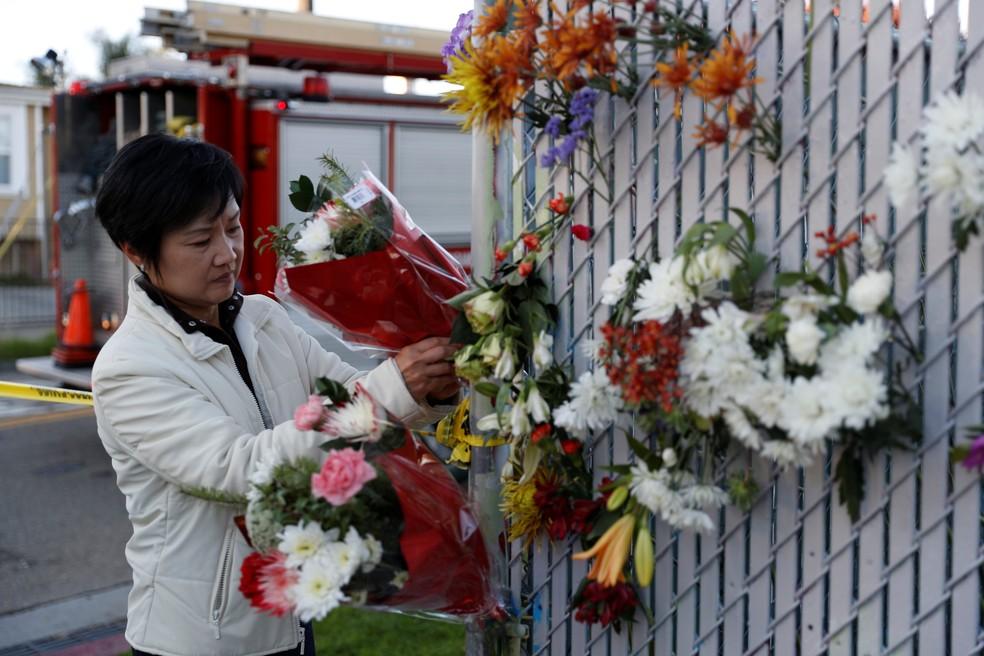 Mulher deposita flores em homenagem às vítimas de incêndio em festa na cidade de Oakland, na Califórnia, neste domingo (4) (Foto: Reuters/Stephen Lam)