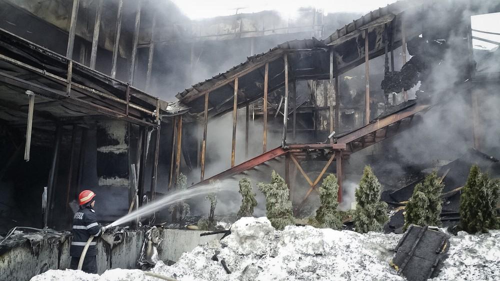 Bombeiros controlam o fogo em casa noturna na Romênia, neste sábado (21) (Foto: ISU via AP)
