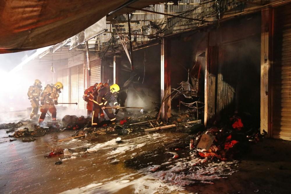 Bombeiros com material em mãos para combater incêndio na Feira dos Goianos (Foto: Corpo de Bombeiros/Divulgação)