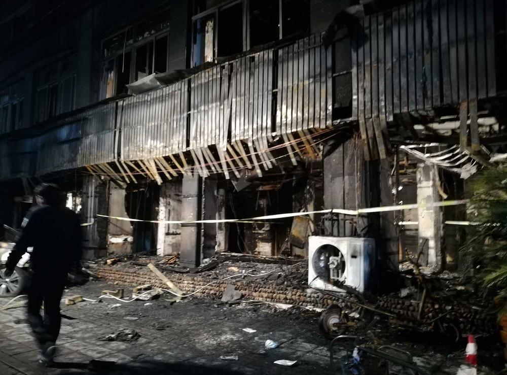 Homem passa na frente de casa de massagem que foi destruída pelo fogo na província de Zhejiang, na China (Foto: Wang Junlu/Xinhua via AP)